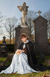 Widow with flowers. Widow in Victorian dress sitting on a tombstone Royalty Free Stock Image