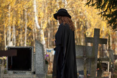 Widow looking at the gravestone. Lonely widow dressed in black standing over her husband's gravestone Stock Images