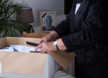 Widow packing stuff. Elderly widow packing stuff to the box Stock Photos