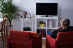 Widow sitting in living room. Pensive widow sitting alone in living room Royalty Free Stock Image