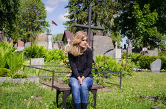 Widow woman soldier lover grave. Lithuania flag. Sad woman sit near lover grave in cemetery. Patriot soldier died. National Lithuania flag Royalty Free Stock Photos