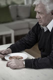 Widower eating meal Royalty Free Stock Photo