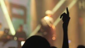 Widownia leje się w dół od sceny nad z rękami podnosić przy festiwalem muzyki i światłami blured tło zbiory wideo
