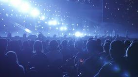 Widownia leje się w dół od sceny nad z rękami podnosić przy festiwalem muzyki i światłami Mnóstwo ludzie z zbiory wideo