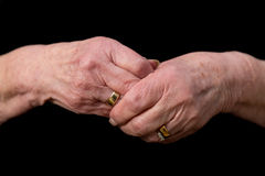 Widows hands clasped in grief on a black background. Widows hands clasped in grief wearing her late husbands wedding ring. Concept of loss, mourning and Stock Photography