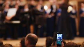Widzowie przy koncertem - zaludnia mknącego występ na smartphone, muzyczna opera zdjęcie royalty free