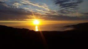 Wie die Sonne und die Lichtstrahlen weiter über den Ozean untergeht Lizenzfreies Stockfoto