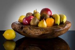 Świeże całe owoc w unikalnym obyczajowym drewnianym pucharze - Wysokiej jakości zdrowy pojęcie na czarnym i szarym tle zdjęcia stock