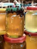 WIE EINE BIENE ZUM HONIG - ein Schwarm von Bienen wird zu einem Stapel Honiggläsern angezogen Stockfoto