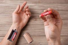 Wie man die Energie der Liebe neulädt Wort LIEBE wird auf die Batterie geschrieben Hand eines Mannes mit einem Schlitz für Auflad Lizenzfreie Stockfotos