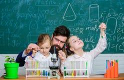 Wie man Kinder interessiert zu studieren Faszinierende Biologielektion Bärtige Lehrerarbeit des Mannes mit Mikroskop und Reagenzg stockfotos