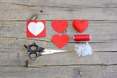 Wie man nähen Sie ein Filzherz für Valentine's-Tag übergibt referenten Rotfilzherz Lizenzfreie Stockfotos