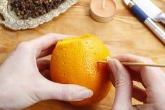 Wie man orange Pomanderball mit Kerze - Tutorium macht Stockfotos