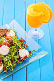 Świeża arugula sałatka z beetroot, koźlim serem, chlebów plasterkami i orzechami włoskimi na szklanym talerzu na błękitnym drewni Zdjęcie Royalty Free