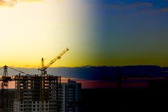 Wieczór budowa z wysokim żurawiem przeciw tłu pogodny zmierzch z czerwonym niebem zdjęcie stock