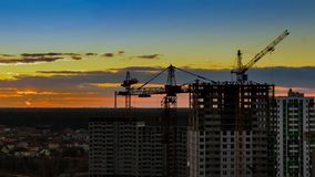 Wieczór budowa z wysokim żurawiem przeciw tłu pogodny zmierzch z czerwonym niebem fotografia royalty free