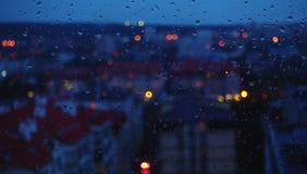 Wieczór miasta, okno i deszczu krople, Obrazy Stock