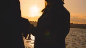 Wieczór sylwetka urocza para, stojaki przy jeziorem z zmierzchem jarzy się zbiory
