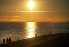 Wieczór zmierzch na tle woda morska i ludzie chodzić obraz stock