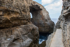 Wied il Mielah canyon, natural arch over the sea. Gozo, Malta. Wied il Mielah canyon and natural arch over the sea in Gozo, Malta Royalty Free Stock Photography