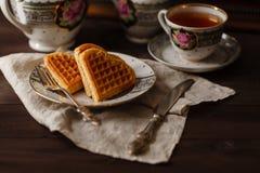 Wiedeńscy opłatki na zmroku stole z herbacianą filiżanką zdjęcie stock