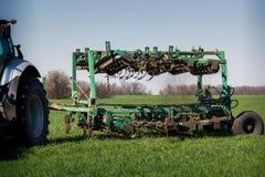 wieden-machine achter tractor op groen tarwegebied stock afbeelding