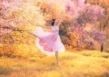 Wieder belebte Porzellanpuppe, wenn rosa Kleidertanzen in bl?hendem Fr?hlingswald, zarte Dame mit dem dunklen Haar in hellem gefl lizenzfreies stockbild