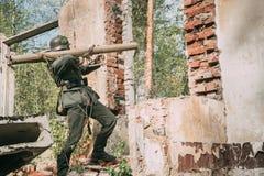 Wieder--enactor gekleidet als offenes Feuer Deutscher Wehrmacht-Infanterie-Soldat-In World Wars II von der Panzerabwehr- Kanone w lizenzfreie stockfotografie