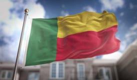 Wiedergabe Benin-Flaggen-3D auf blauer Himmel-Gebäude-Hintergrund Stockfoto