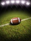 Wiedergabe 3d eines Fußballs auf einem Feld mit Stadionsbeleuchtung Stockfotos