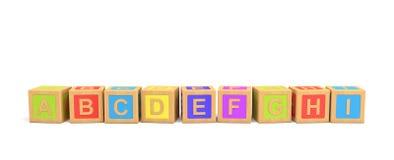 Wiedergabe 3d einiger hölzerner Spielzeugziegelsteine mit englischen Buchstaben in der alphabetischen Reihenfolge auf einem weiße Lizenzfreie Stockfotografie