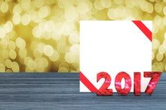 Wiedergabe 3D: helle bokeh 2017 Zahl und weiße Karte mit rotem Band auf hölzernem Schreibtisch der Perspektive funkelnder bokeh W Lizenzfreies Stockfoto