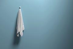 Wiedergabe 3D: Illustration eines Stückes des sauberen und weißen Tuches, das an einer blauen Pastellwand, an einem Licht und an  Stockfoto