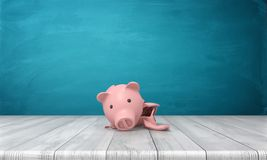Wiedergabe 3d von einem defekten Sparschwein in einigen großen Scherben, die auf einem hölzernen Schreibtisch liegen Lizenzfreie Stockfotos