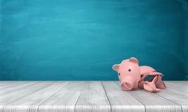 Wiedergabe 3d von einem defekten Sparschwein in einigen großen Scherben, die auf einem hölzernen Schreibtisch liegen Stockfotos
