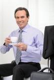 Wiederherstellung seiner Energie. Netter reifer Geschäftsmann trinkendes coffe Lizenzfreies Stockfoto