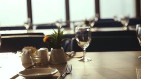 Wiederholen Sie Halle mit verzierter Tabelle, Tischbesteck und Stühlen im Restaurant, das für Heiratsfeier während des Sonnenunte stock footage
