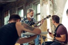 Wiederholung der Rockmusikband E-Gitarren-Spieler und Schlagzeuger hinter dem Trommelsatz lizenzfreie stockfotos