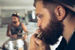 Wiederholung der Rockmusikband Mann mit Harmonika und Schlagzeuger hinter dem Trommelsatz stockfoto