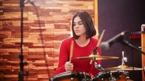 wiederholung Mädchen in der roten Strickjacke spielt inbrünstig die Trommeln in einem Studio stock video