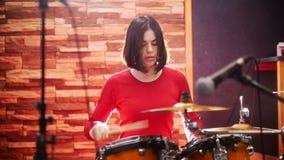 wiederholung Mädchen in der roten Strickjacke spielt leidenschaftlich die Trommeln in einem Studio stock video