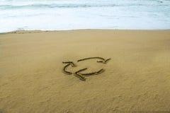 Wiederverwertung das Zeichen gezeichnet auf Sand lizenzfreies stockfoto