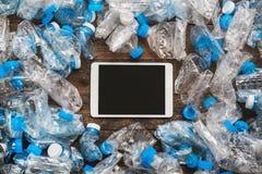 Wiederverwertung des Konzeptes Hölzerner Hintergrund des Tablets um die transparenten Plastikflaschen Das Problem der Ökologie, K Lizenzfreies Stockfoto