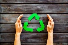 Wiederverwertung des Symbols in den Händen für Ökologie auf Draufsicht des hölzernen Hintergrundes stockfoto
