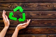 Wiederverwertung des Symbols in den Händen für Ökologie auf hölzernem copyspace Draufsicht des Hintergrundes stockfotografie