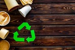 Wiederverwertung des Symbols mit Papier und Plastikschale für Ökologie auf hölzernem copyspace Draufsicht des Hintergrundes lizenzfreie stockfotografie