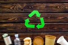 Wiederverwertung des Symbols mit Papierschale, Plastikflasche, Dose für Ökologie auf Draufsicht des hölzernen Hintergrundes stockbilder