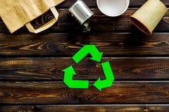 Wiederverwertung des Symbols mit Papiertüte, Schale, Dose für Ökologie auf Draufsicht des hölzernen Hintergrundes stockbild