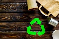 Wiederverwertung des Symbols mit Papiertüte, Schale, Dose für Ökologie auf hölzernem copyspace Draufsicht des Hintergrundes lizenzfreie stockfotos