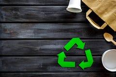 Wiederverwertung des Symbols mit Plastikschale, Papierschale und Tasche, Besteck für Ökologie auf hölzernem copyspace Draufsicht  stockfotografie